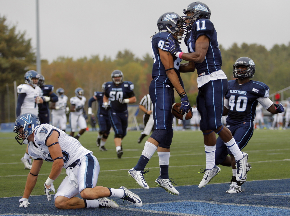 ORONO ME - OCTOBER 4: Arthur Williams, (89) celebrates with teammate Jordan Dunn (11) after Williams caught a 25-yard touchdown pass in the first quarter of a CAA college football game between Maine and Villanova at Alfond Stadium in Orono, Saturday, October 4, 2014. (Photo by Gabe Souza/Staff Photographer)