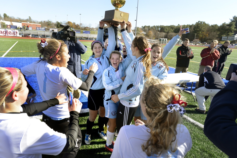 John Patriquin/StaffPhotographer:Sat., Nov.9, 2013. Windham HS girls soccer team hoist the gold ball as they celebrate defeating Bangor for the Maine State Class A Soccer championship at McMann Field in Bath.