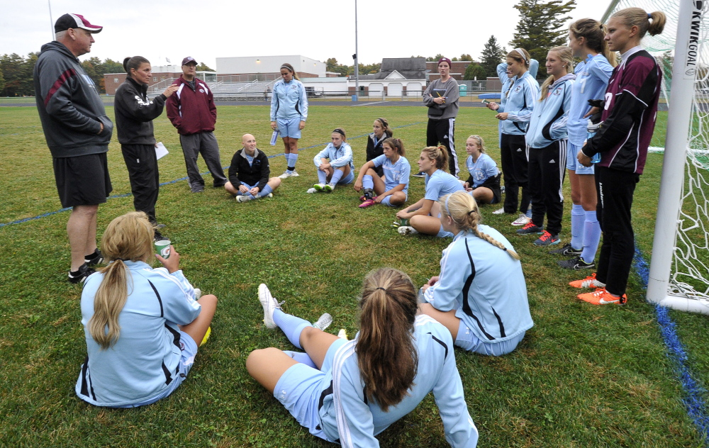 Windham Coach Deb Lebel, second from left, talks to her team at halftime of a recent game. The Eagles won the Class A state title last fall and, with a roster stacked with talented players who play the game year-round, are the favorites to win it again this fall. They are off to a 9-0 start.