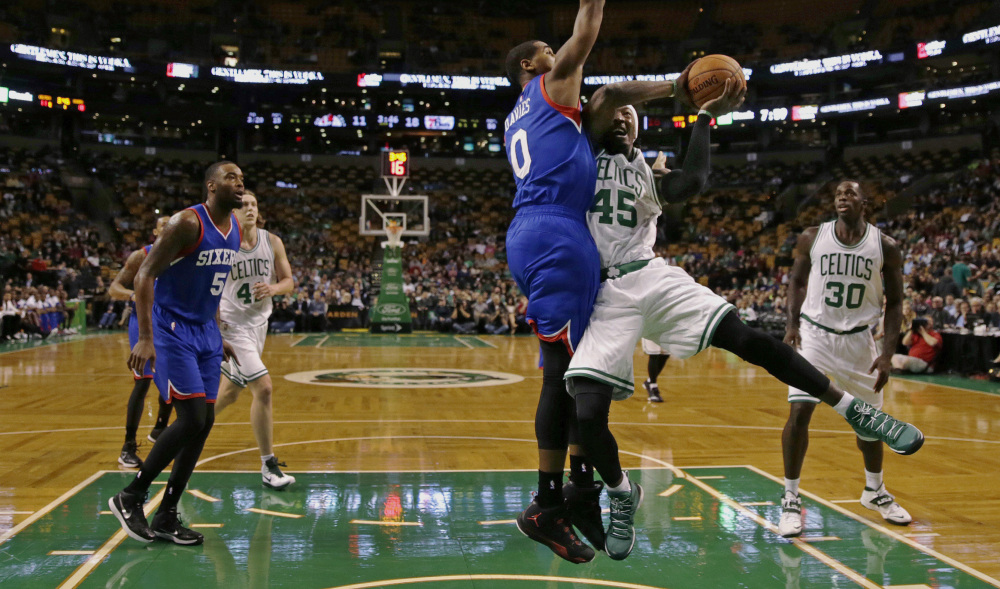 Philadelphia 76ers forward Brandon Davies (0) blocks Boston Celtics forward Gerald Wallace (45) on a drive to the basket during the first quarter of a preseason NBA basketball game in Boston, Monday, Oct. 6, 2014. (AP Photo/Charles Krupa)