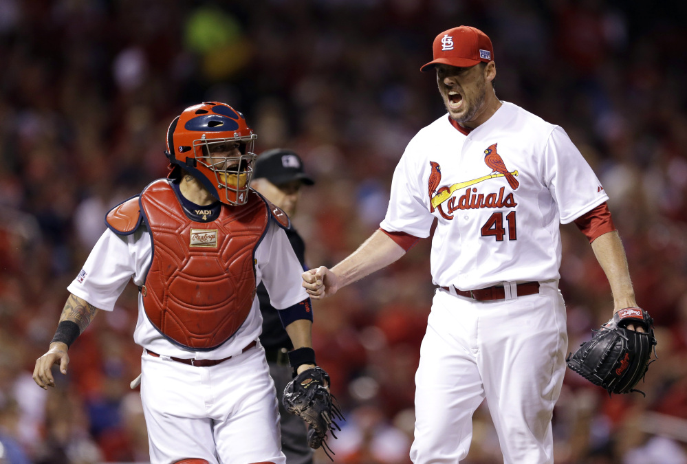 St. Louis Cardinals pitcher John Lackey reacts with catcher Yadier Molina after throwing out the Los Angeles Dodgers' Carl Crawford at first base in the fourth inning of Game 3 of the NL Division Series on Monday in St. Louis.