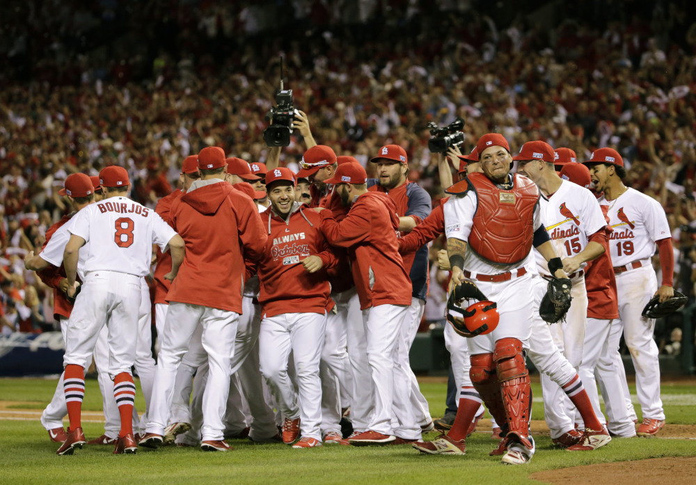 St. Louis Cardinals players celebrate their 3-2 win Tuesday over the Los Angeles Dodgers in Game 4 of the NL Division Series in St. Louis. The Cardinals won the best-of-five series in four games.