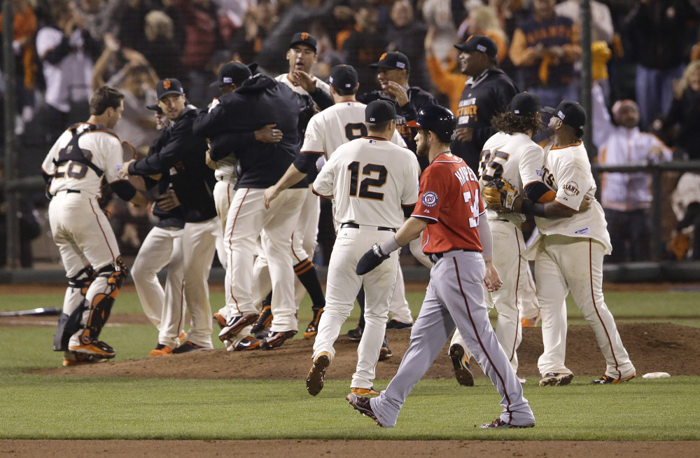The San Francisco Giants celebrate after beating the Washington Nationals on Tuesday night in Game 4 of the NL Division Series in San Francisco. The Giants won the best-of-five series in four games.