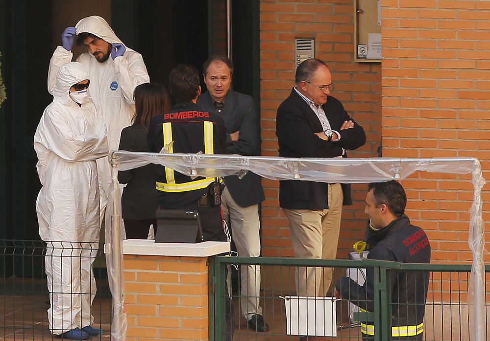 Firemen stand as worker wearing rompers and gloves come out ofthe building entrance of the apartment building of the Spanish nurse infected with Ebola in Madrid, Spain, Wednesday.