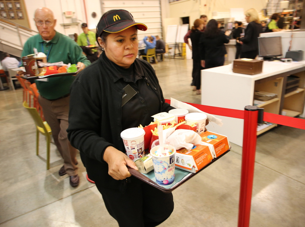 McDonald employees, trainees and staff carry back trays of food at a simulated Australian restaurant at the McDonald's Innovation Center in Romeoville, Ill. Antonio Perez/Chicago Tribune/MCT