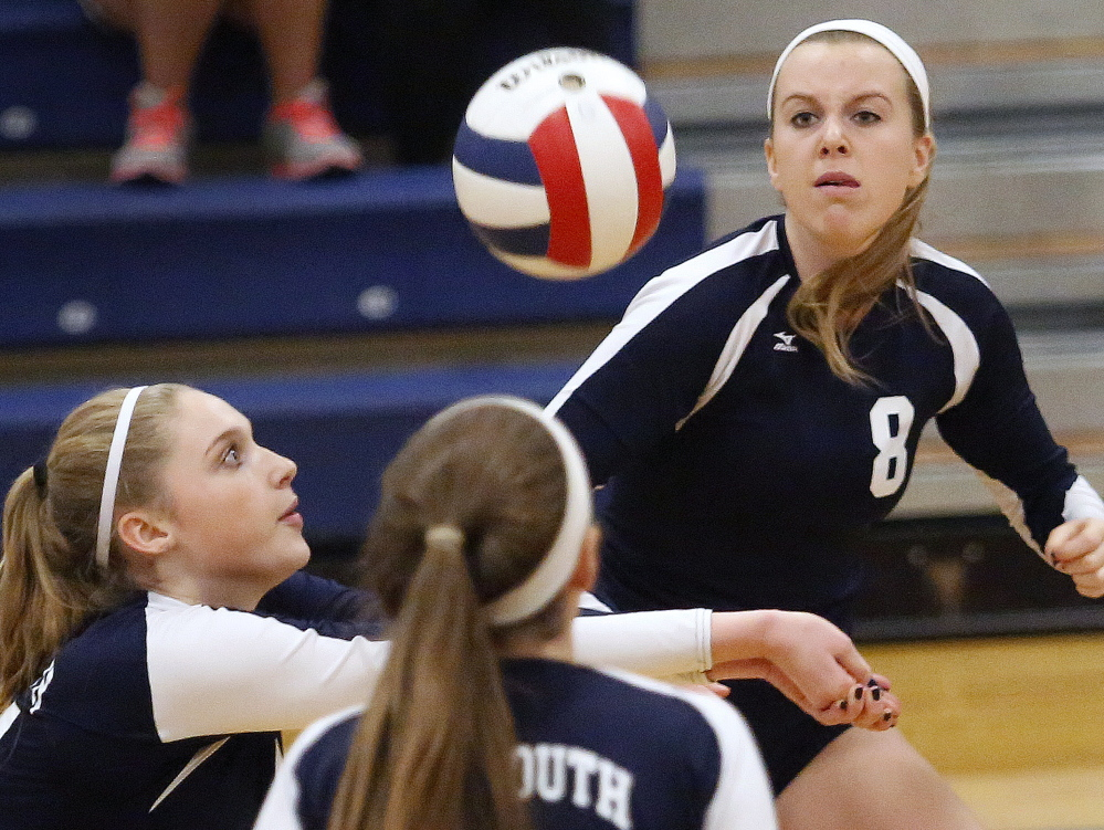 Alison Clark of Yarmouth prepares to hit the ball as Emily Parker, at right, keeps her eyes locked on the ball, and teammate Noelle Yunker, looks on during Yarmouth's 3-0 Class B volleyball semifinal victory at home.