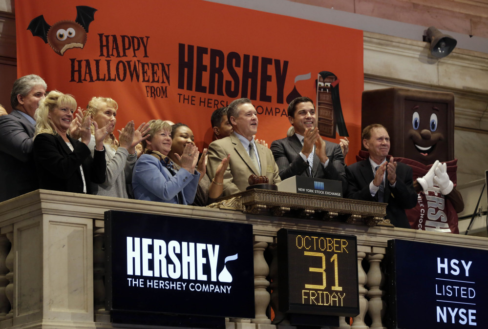 J.P. Bilbrey, president and chief executive officer of The Hershey Company, center, is applauded, including by a Hershey bar at right, as he rings the New York Stock Exchange opening bell Friday.
