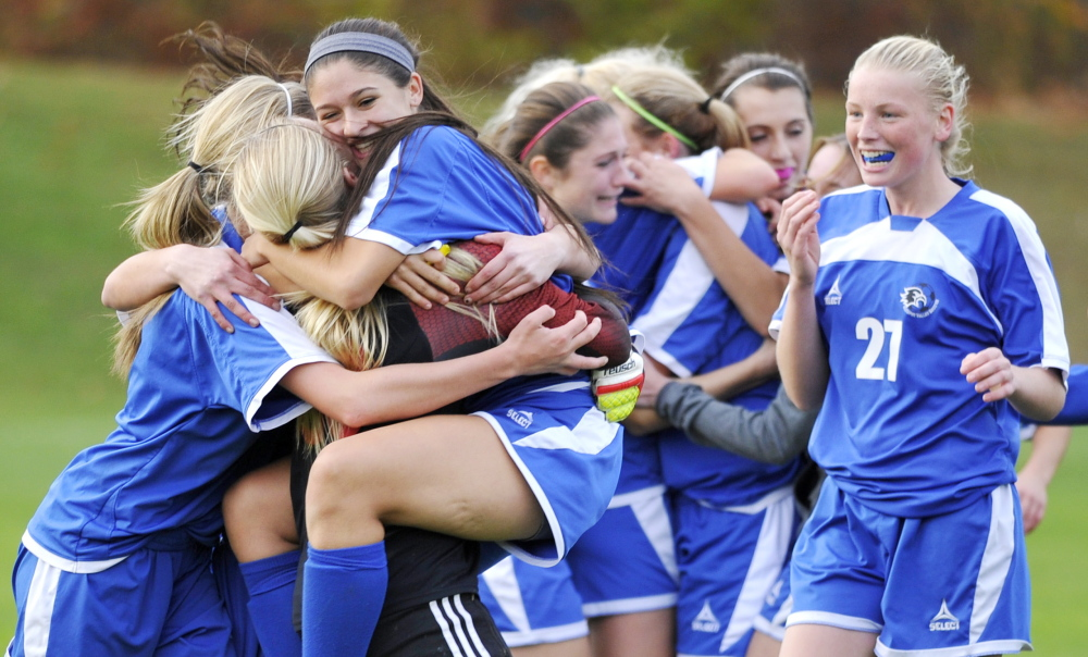 Jade Jordan jumps into the arms of keeper Madison Day as Sacopee Valley celebrates its 1-0 win over Waynflete in an Western Class C girls' soccer semifinal Friday in Portland. Day made five saves to help the Hawks avenge a loss to Waynflete in last year's regional final.