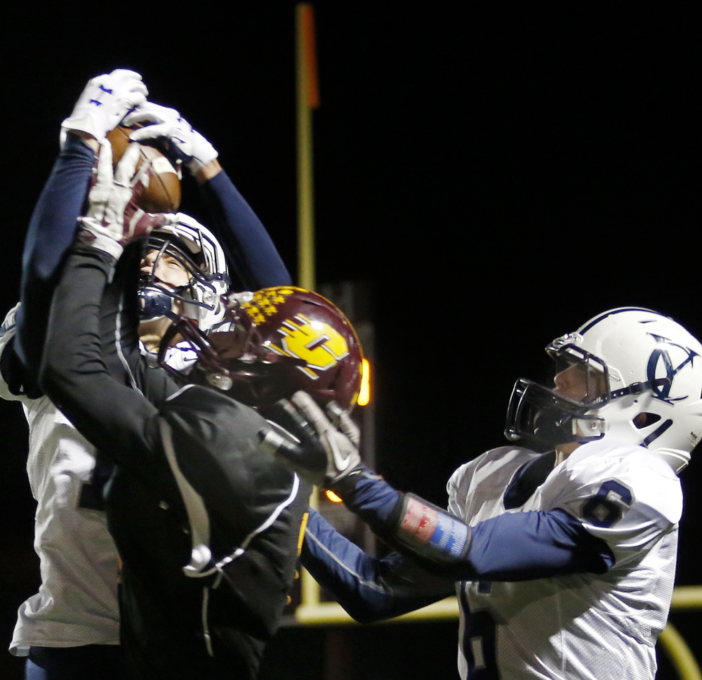 Cody Cook, left, of Yarmouth, intercepts a pass intended for Peyton Weatherbie of Cape Elizabeth while Jack Snyder also defends Friday night during a Western Class C football quarterfinal in Cape Elizabeth. Yarmouth won, 14-12.