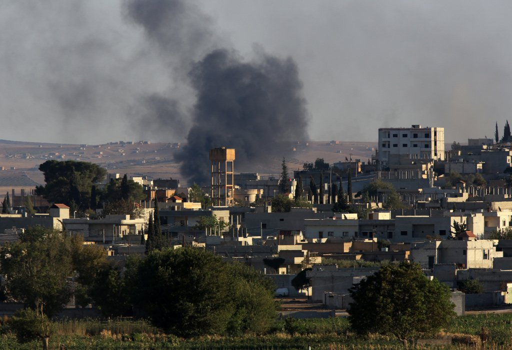 Smoke rises after a mortar shell landed in the south of the city center of Syrian Kurdish town of Kobani, seen from the Turkish side of border, as thousands of new Syrian refugees from Kobani arrive in Suruc, Turkey on Wednesday,. The Associated Press