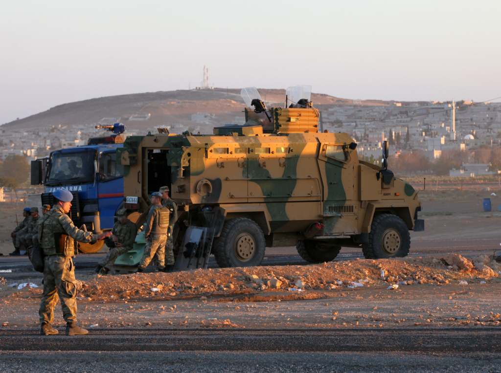 Turkish soldiers stand guard at a checkpoint as Syrian refugees from Kobani arrive at the Turkey-Syria border crossing of Mursitpinar near Suruc, Turkey, late Wednesday. The Associated Press