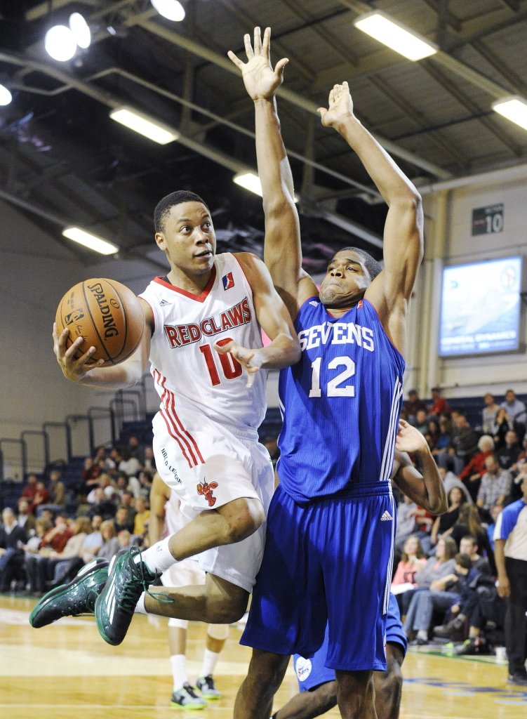 Maine's Tim Frazier sdrives the lane against Delaware's Ronald Roberts Jr. during the Red Claws' 120-102 win Sunday. John Ewing/Staff Photographer