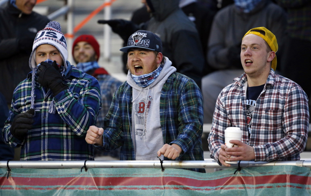 Maine fans cheer during a college football game between Maine and New Hampshire on Saturday in Orono. Organizers hoped to boost attendance at the chilly event by giving away bandannas, below, in a shot at setting a Guinness world record. Photos by Robert F. Bukaty/The Associated Press