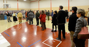 District 1 Warden Philip Gaven (left) hands out sample ballots to people waiting to vote at the Boys and Girls Clubs in South Portland.
