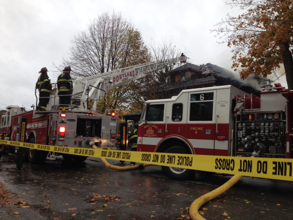 Firefighters douse the flames from the fire Saturday morning on Noyes Street in Portland.
