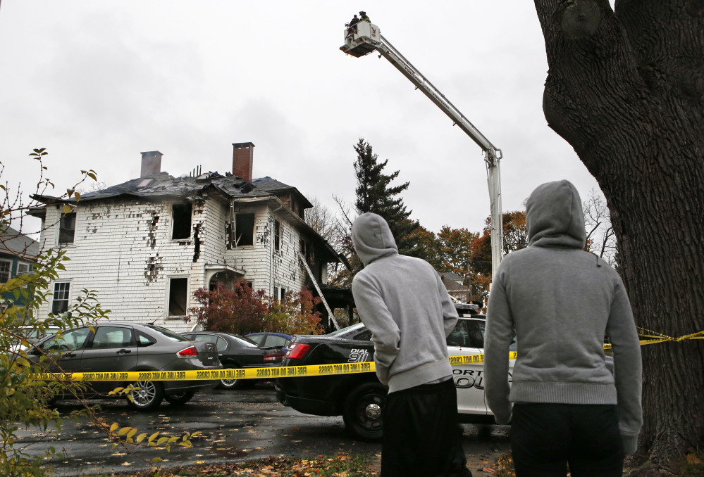 Neighbors look at the scene of a fatal apartment building fire, Saturday, Nov. 1, 2014, in Portland, Maine. The fire swept through a two-apartment building housing students from the University of Southern Maine on Saturday morning, killing four people and critically injuring one, authorities said. They were still trying to account for several people who had been at a Halloween party at the building the night before. (AP Photo/Robert F. Bukaty)