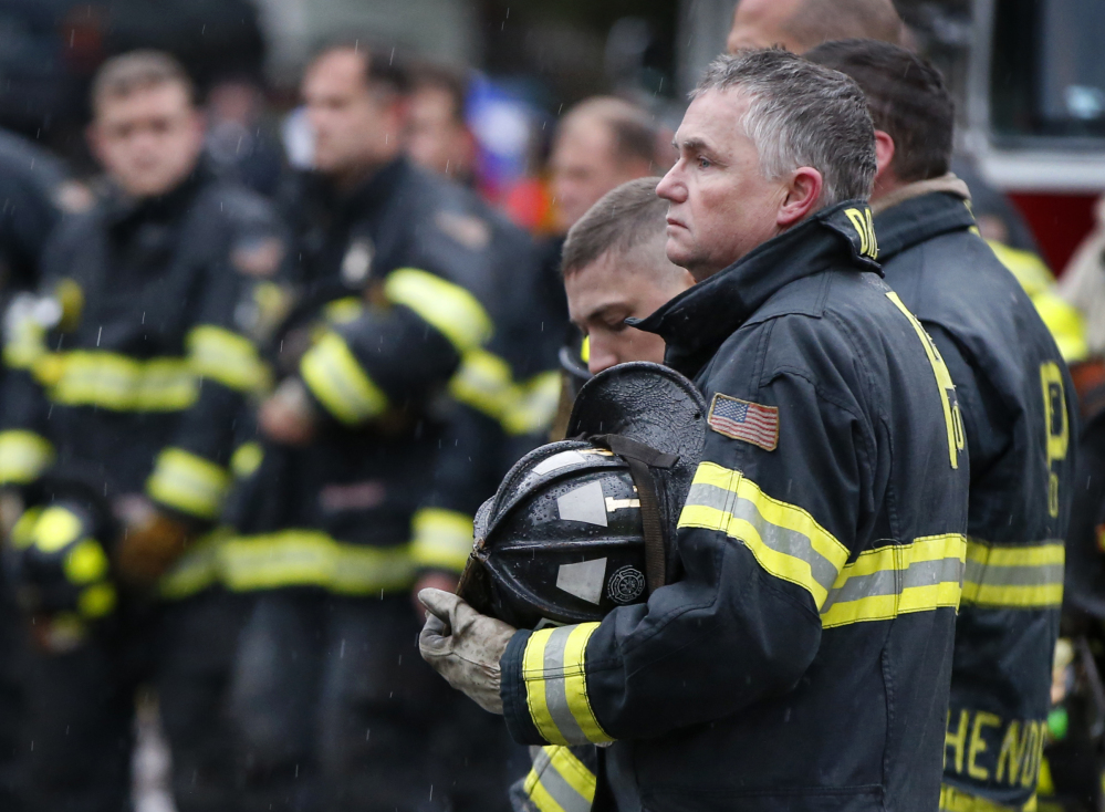 Firefighters take their helmets off as a body is removed from the scene of the fatal apartment building fire in Portland on Saturday.