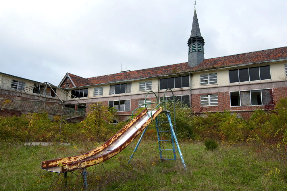 A rusty children's slide remains on the property at the former Seaside tuberculosis sanatorium, in Waterford, Conn. The sanatorium was designed in 1913 by noted architect Cass Gilbert for children who suffered from tuberculosis.