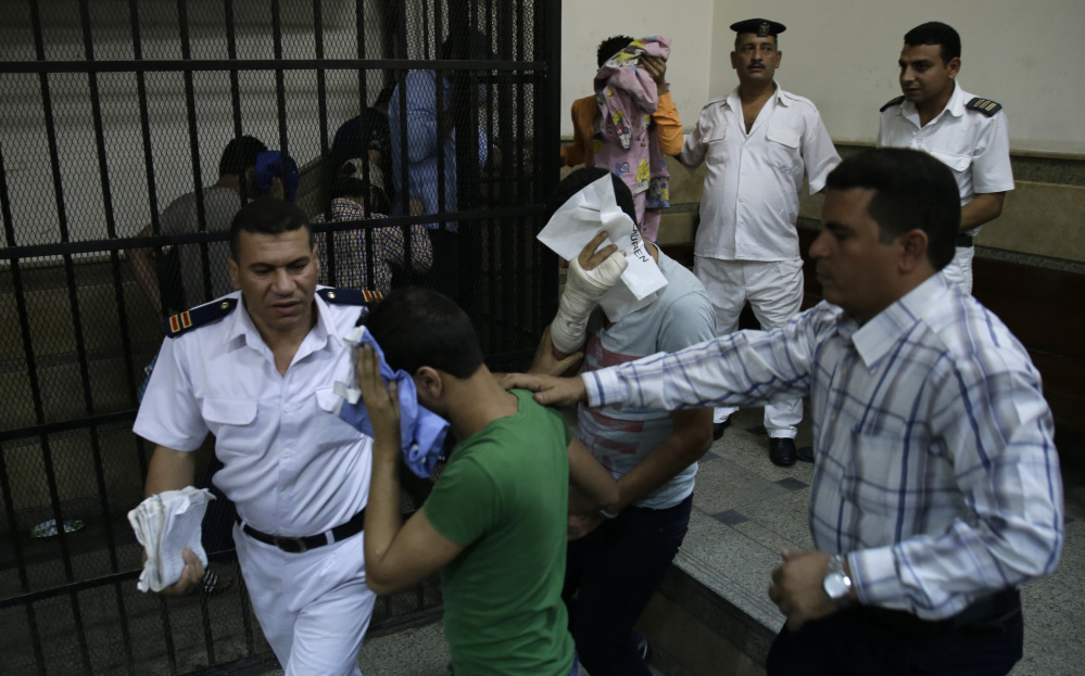 """Egyptian men convicted of """"inciting debauchery"""" after an alleged same-sex wedding party cover their faces as they leave court in Cairo, Egypt, on Saturday."""