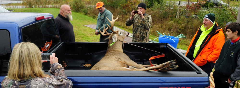A buck weighing more than 200 pounds, shot by Mike Bennett, center in an orange hat, draws a lot of attention Saturday at Audette's Hardware in Winthrop.
