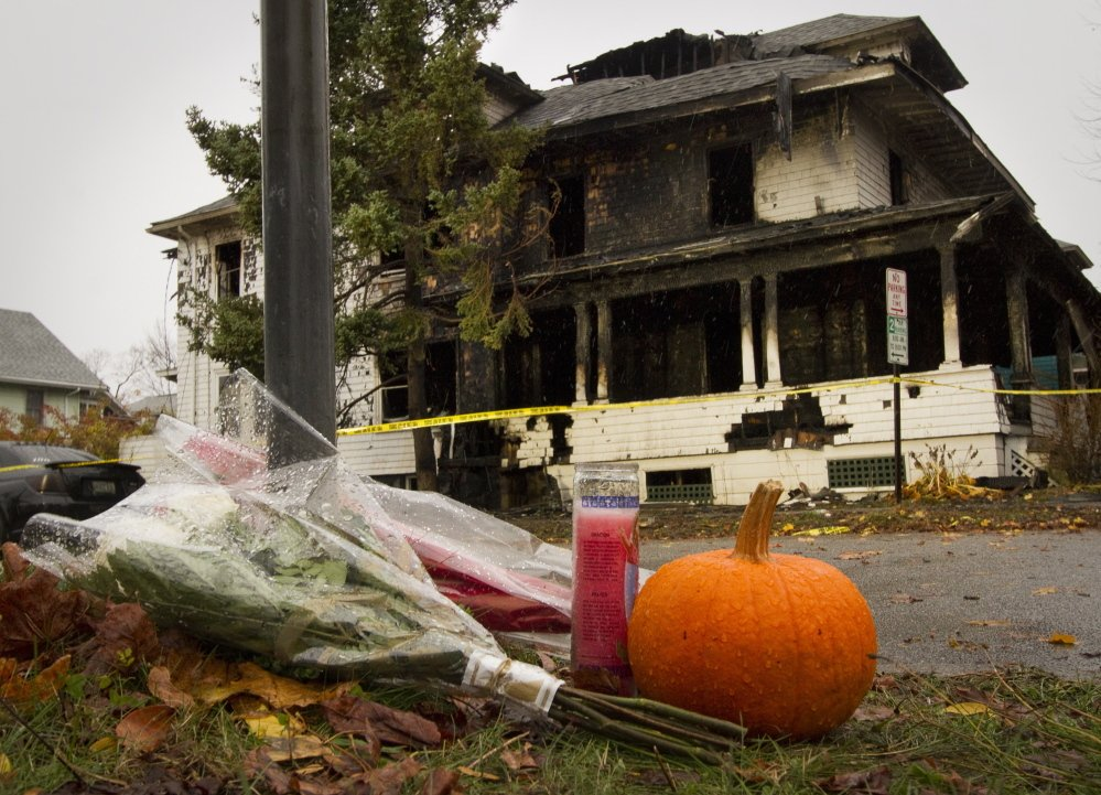 A shrine starts to grow Sunday morning on Noyes Street near the scene of a house fire that claimed five lives Saturday.