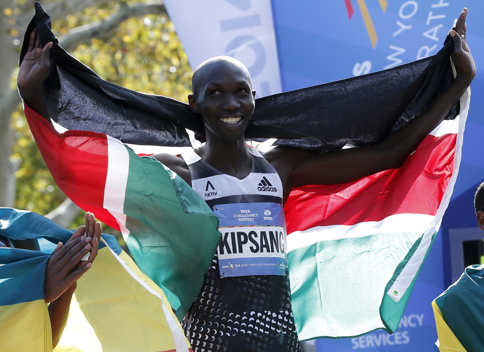 Wilson Kipsang of Kenya celebrates with his country's flag after winning the 2014 New York City Marathon in Central Park in Manhattan on Sunday.