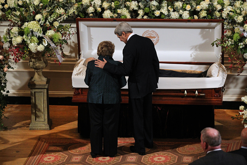 Secretary of State John Kerry and Angela Menino, widow of former Boston Mayor Tom Menino, stand at the casket as Menino lies in state at Faneuil Hall on Sunday.  Suzanne Kreiter/The Boston Globe