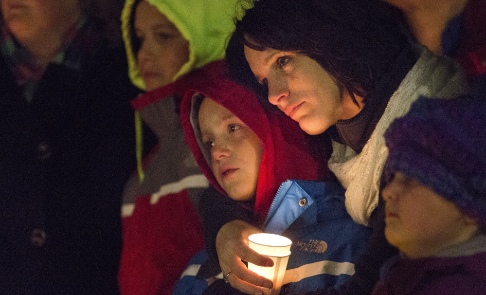 asdfl;kj... CORNISH, ME - NOVEMBER 3: Laura Gerry of Porter holds her son, Dylan Capano, 8, close to her as they comfort each other during a vigil that was held at Call's Shop 'n Save on Route 25 in Cornish Monday evening, November 3, 2014, for the victims of a car crash that killed two teenagers in Hiram early Saturday morning. Andrew Stanley, 18, of Porter, died at the scene, and Isaac Moore, 19, of Parsonsfield, died at Maine Medical Center. (Photo by Gabe Souza/Staff Photographer)