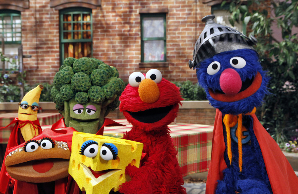 """This June 22, 2010 file photo released by Sesame Workshop, """"Sesame Street"""" characters Elmo, second from right, and Super Grover, right, pose with four new muppets representing healthy food groups; fruits, vegetables, dairy, and grains as part of their """"Food For Thought:  Eating Well on a Budget"""" initiative in New York."""