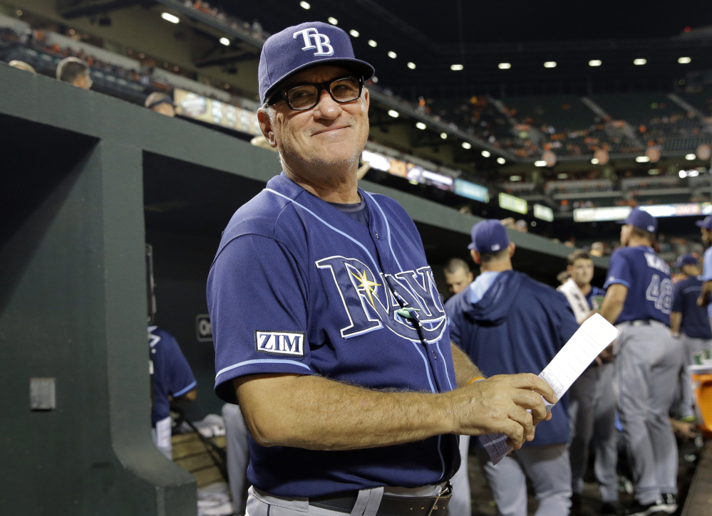 In this Aug. 27, 2014, file photo, Tampa Bay Rays manager Joe Maddon smiles at a fan in the stands in the fifth inning of a baseball game against the Baltimore Orioles in Baltimore.