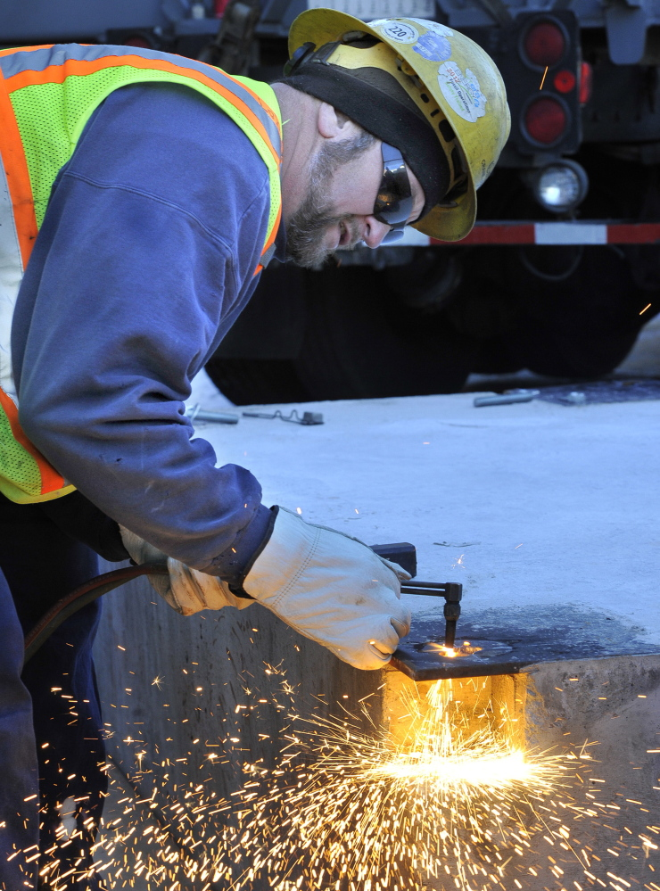 Mike Labbe cuts holes for bolts that will hold the 8-foot-tall sculpture in place.