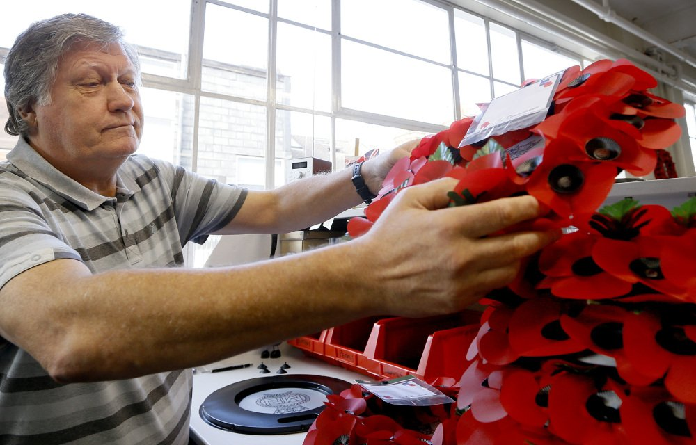 William Sellick, a former soldier who served in Northern Ireland, makes a wreath at the Poppy Factory in Richmond near London on Thursday. He finds the work helps him to face a life shadowed by depression and alcoholism.