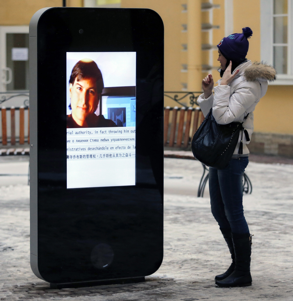 A woman looks at a screen showing a portrait of Steve Jobs on the memorial to the late Apple Corp. co-founder in 2013.