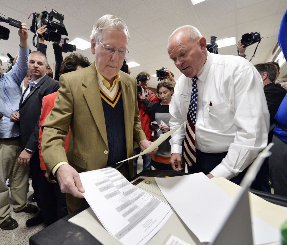 Senate Minority Leader Mitch McConnell of Ky., left, casts his vote as poll worker William Comstock looks on in Louisville, Ky., Tuesday.