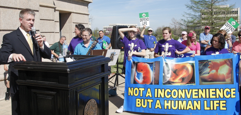 Former Oklahoma state Rep. Kevin Calvey, left, talks Monday to anti-abortion activists at a rally in Oklahoma City, where the issue arouses strong feelings on both sides.
