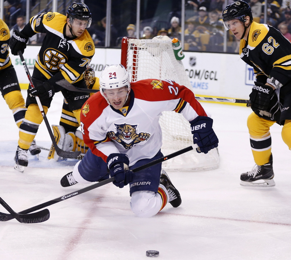 Brad Boyes of the Panthers struggles for control of the puck in front of Boston's Zach Trotman, right, in the first period Tuesday night in Boston. The Bruins won 2-1 in overtime for their third straight win.
