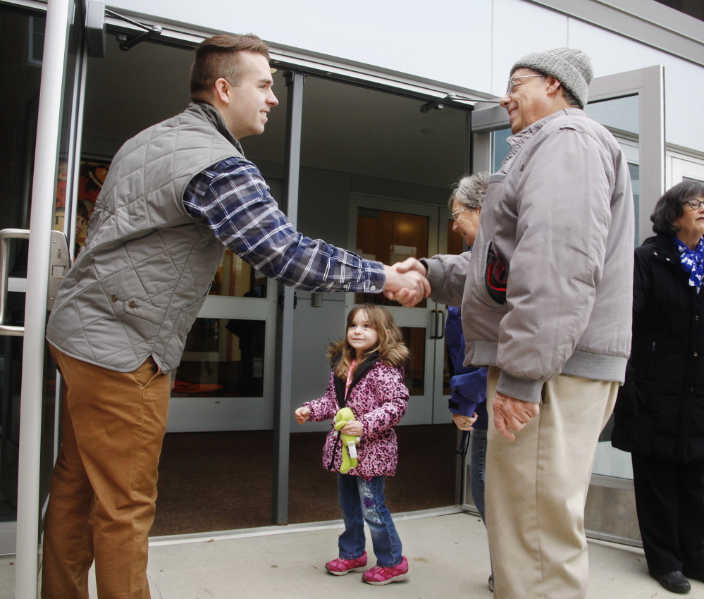 Ryan Fecteau, left, greets Conrad Houde, his wife, Jeanne, and their 3-year-old granddaughter, Aleisha, at Biddeford High School while campaigning for a seat in House District 11 on Tuesday.