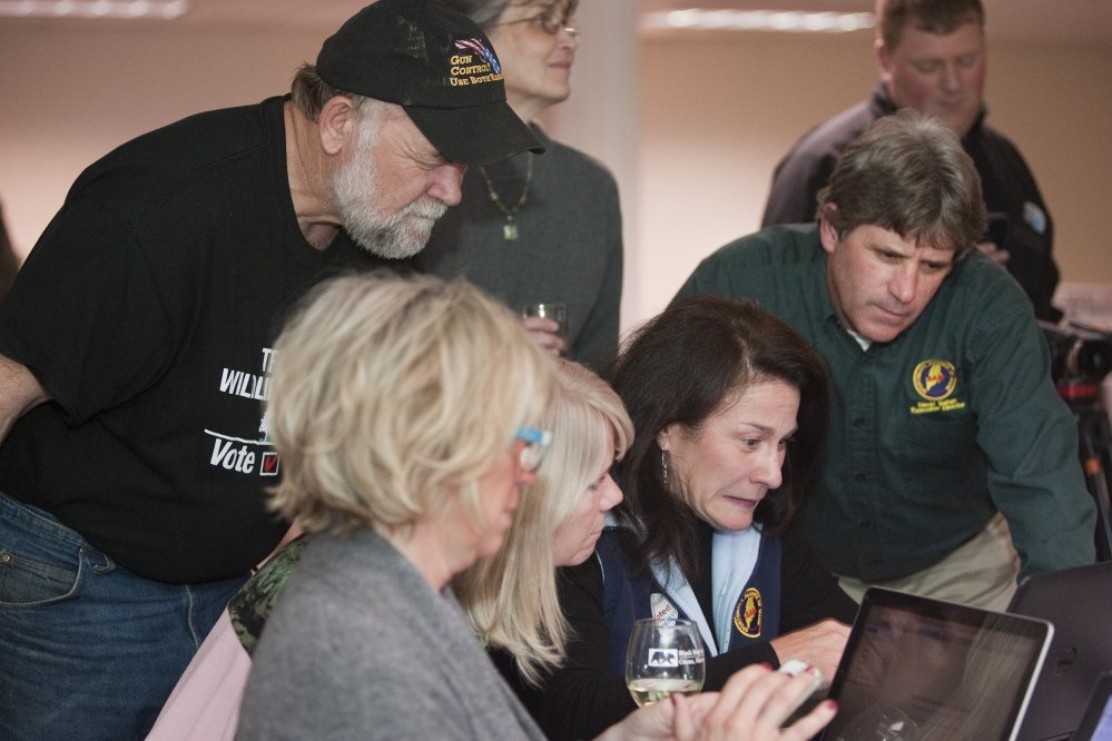 Keith Thompson of Morrill, left, a volunteer with the No on 1 campaign, Sportsmen's Alliance of Maine President Cheryl Timberlake, second from right, and its Executive Director David Trahan, right, monitor online vote returns  at the Black Bear Inn in Orono.