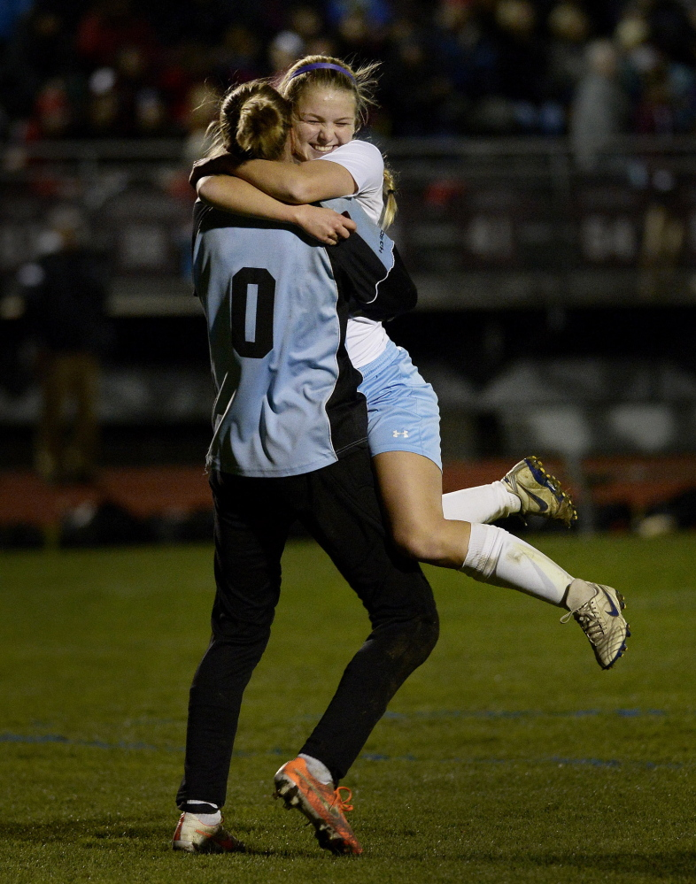 Jordan Sargent jumps into the arms of goalie Elizabeth Mycock after Windham defeated Scarborough 2-1 in the Western Class A girls' soccer title on Wednesday.
