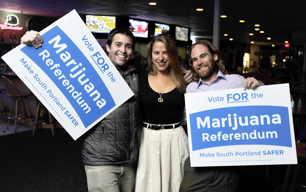 Matthew Bourgeois, Erin Daly and Chris Blake, volunteers for the passage of the marijuana referendum, show their joy with the passing in South Portland, at Thatchers in South Portland.