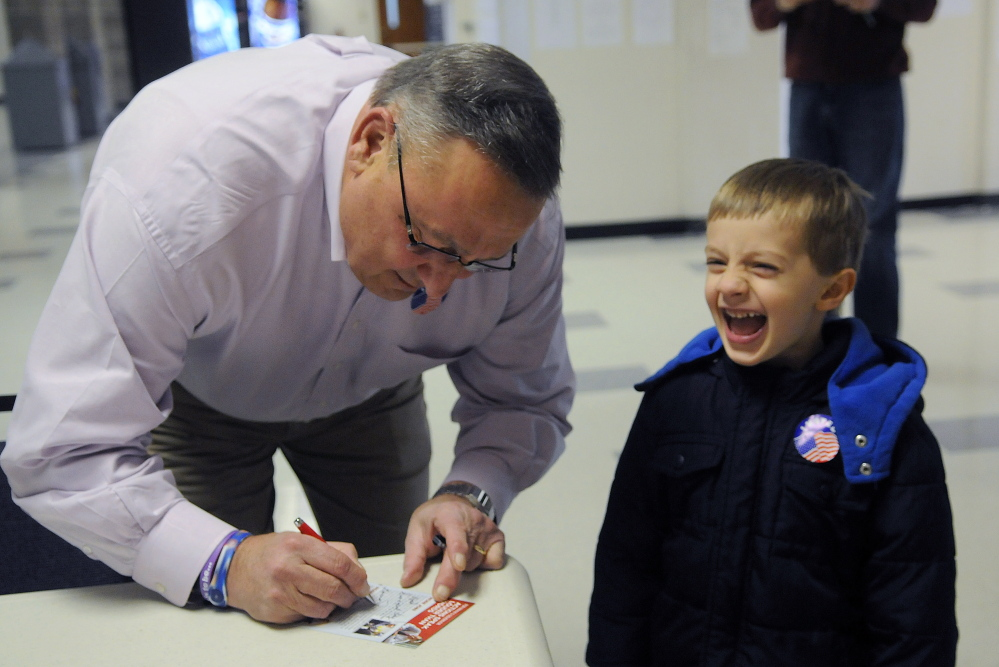 Gov. Paul LePage signs a leaflet Tuesday for a youngster at a polling place in Augusta. The governor ran a campaign that touched the electorate's concerns about the economy.