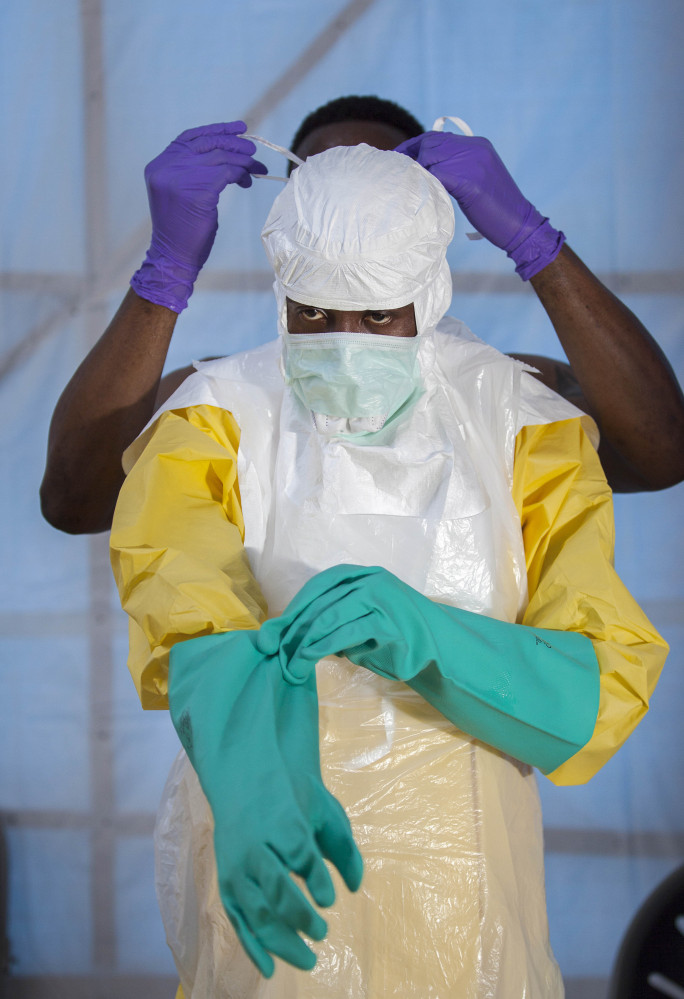 A health care worker in Sierra Leone is tested on protection equipment procedure.