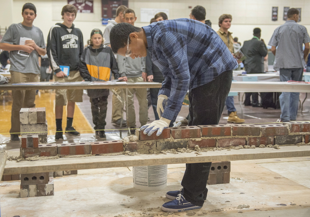 Windham High School sophomore Trevor Rogers adds bricks to a simulated wall during an interactive career fair Thursday at the school.