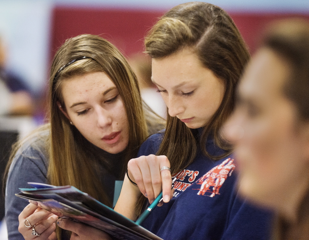 Melanie Aldrich, left, and Joelle Bochus, both juniors at Windham High, check out a  University of New Hampshire brochure at the fair.