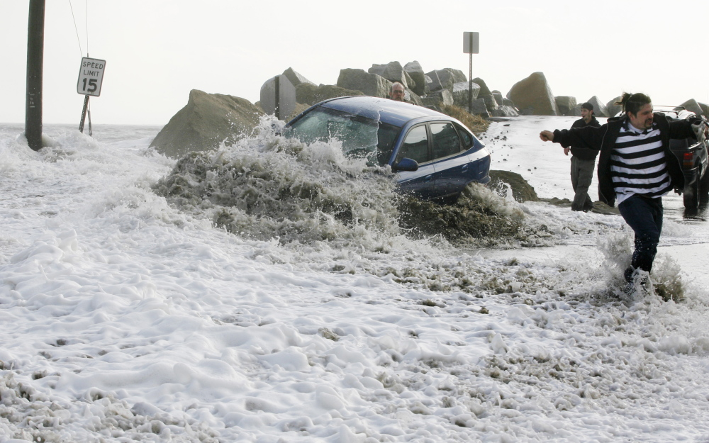 A wave breaks over an occupied car as people try to tow it to safety on Feb. 26, 2010, at Camp Ellis in Saco. The driver left the car as the tide continued to rise, flooding local streets.
