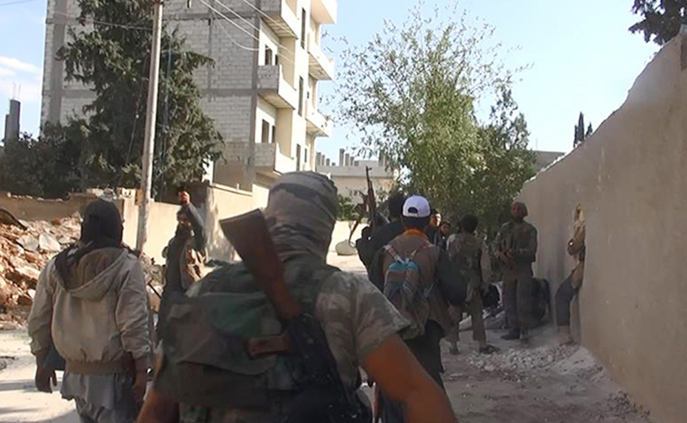 Islamic State group fighters walk through an area in Kobani, Syria. The prolonged stalemate there is a setback for Islamic State militants and has potential implications for recruitment and support.