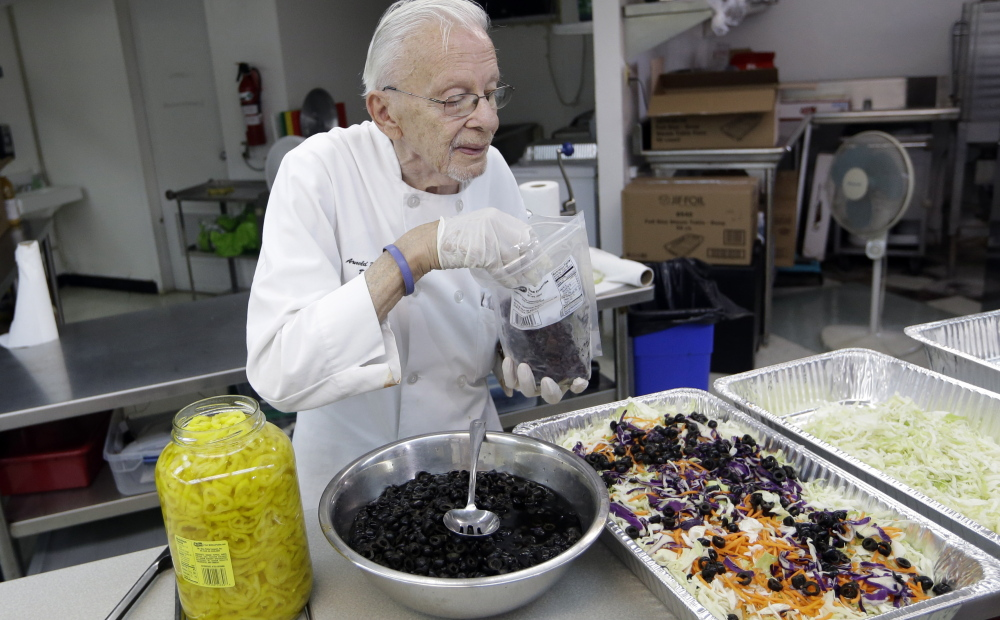 Homeless advocate Arnold Abbott, 90, director of the nonprofit group Love Thy Neighbor Inc., prepares a salad in the kitchen of The Sanctuary Church on Wednesday in Fort Lauderdale, Fla. The Associated Press