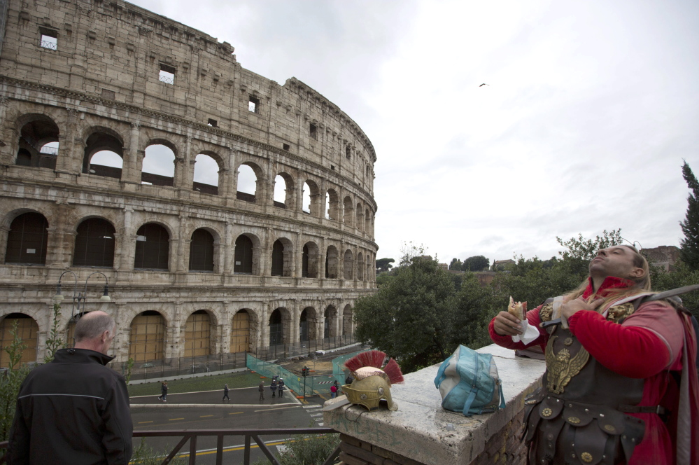 A man dressed as a gladiator enjoys his lunch in front of Rome's Colosseum, on Friday. An archaeologist's proposal to return the Colosseum's storied arena to its original state has sparked a lively debate over appropriate uses of the monument that symbolizes the glories of ancient Rome. Critics have fretted that the Colosseum would be turned into a venue for events like rock concerts, viewed as both unbefitting its stature as an ancient wonder and likely to inflict damage to the structure already weakened by earthquakes, notably in 443 and most recently in the 1700s.