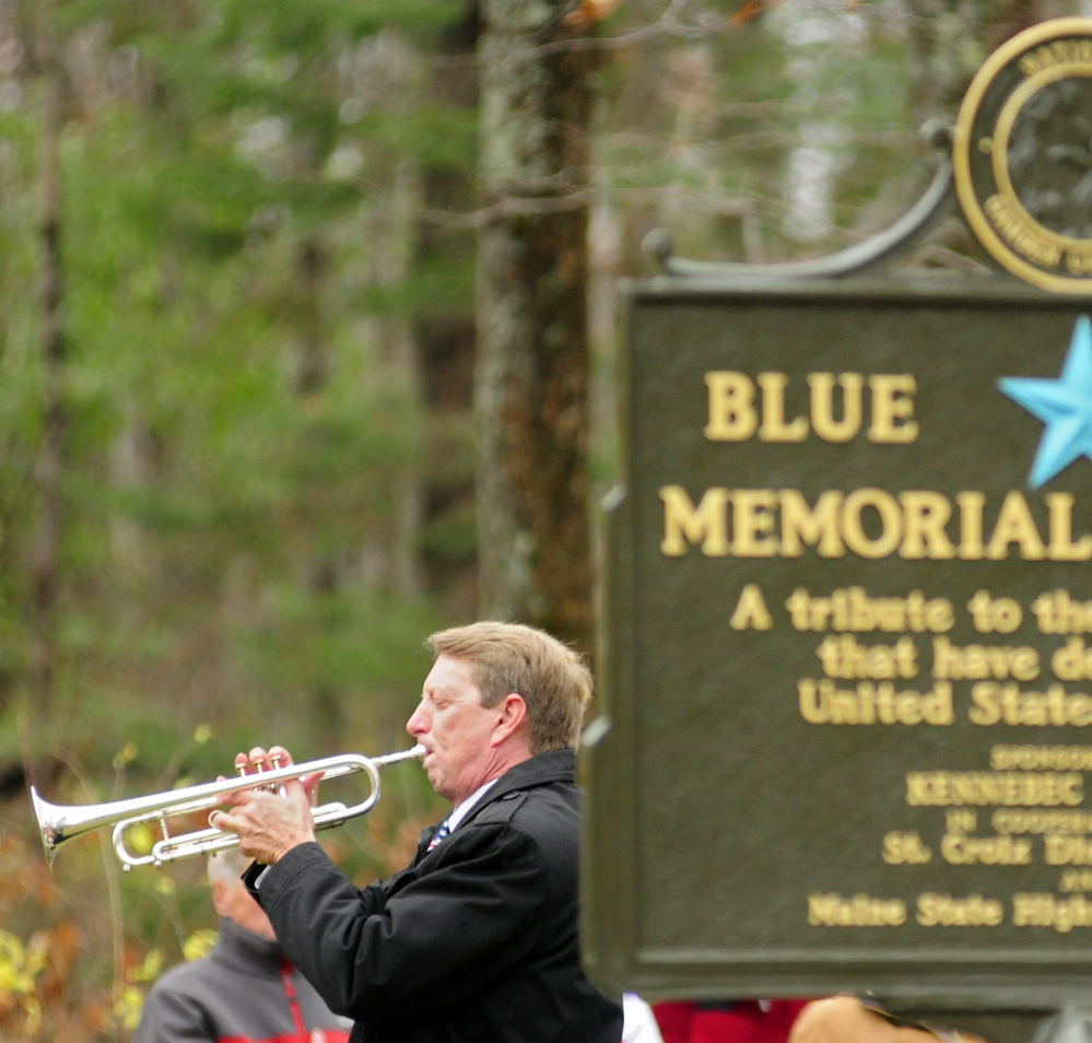 Dwight Tibbetts plays taps at the end of the dedication ceremony in Augusta.