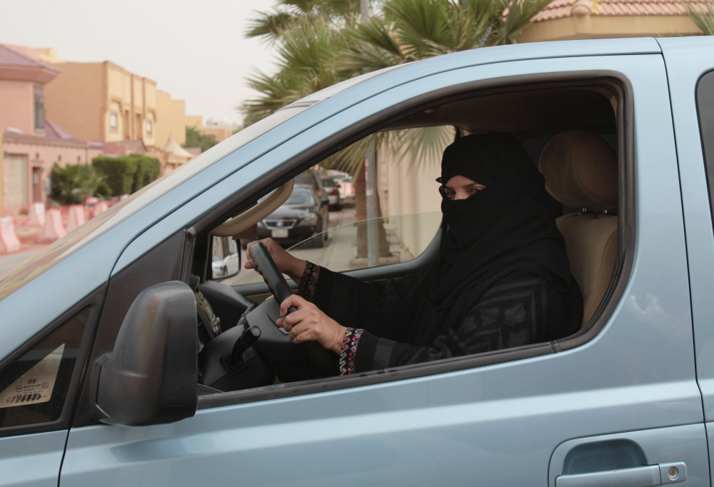 In this photo  from March 2014, Aziza Yousef drives a car in Riyadh, Saudi Arabia, as part of a campaign to defy Saudi Arabia's ban on women driving. A Saudi official said Friday that the kingdom's advisory council has recommended to the government for the first time the partial lifting of the ban on women driving, but with conditions: Only women over 30, only during the day, and no makeup allowed while driving.
